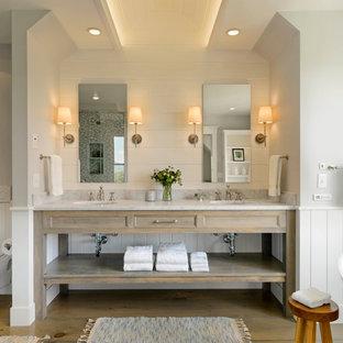 バーリントンのカントリー風おしゃれなマスターバスルーム (アンダーカウンター洗面器、オープンシェルフ、ヴィンテージ仕上げキャビネット、置き型浴槽、壁掛け式トイレ、白い壁) の写真