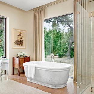 Imagen de cuarto de baño mediterráneo con bañera exenta, ducha esquinera, baldosas y/o azulejos beige, paredes beige y suelo de madera en tonos medios