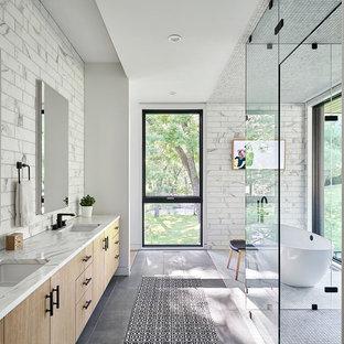 カンザスシティのコンテンポラリースタイルのおしゃれなマスターバスルーム (フラットパネル扉のキャビネット、淡色木目調キャビネット、置き型浴槽、バリアフリー、グレーのタイル、白いタイル、アンダーカウンター洗面器、グレーの床、白い洗面カウンター) の写真