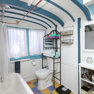 Imagen de cuarto de baño con ducha, ecléctico, de tamaño medio, con bañera exenta, combinación de ducha y bañera, sanitario de dos piezas, paredes azules, suelo de baldosas de cerámica, suelo violeta y ducha con cortina