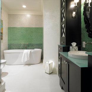 Foto de cuarto de baño mediterráneo con lavabo sobreencimera, armarios estilo shaker, puertas de armario negras, bañera exenta, baldosas y/o azulejos verdes, baldosas y/o azulejos en mosaico, paredes blancas, encimera de vidrio y encimeras turquesas