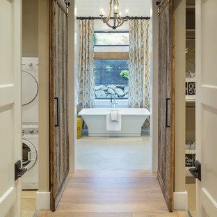 Example of a transitional light wood floor freestanding bathtub design in Portland