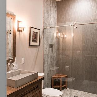 Diseño de cuarto de baño con ducha, rústico, de tamaño medio, con armarios con paneles empotrados, puertas de armario de madera en tonos medios, ducha empotrada, sanitario de dos piezas, baldosas y/o azulejos grises, baldosas y/o azulejos de porcelana, paredes grises, lavabo sobreencimera, encimera de madera, ducha con puerta corredera y encimeras marrones