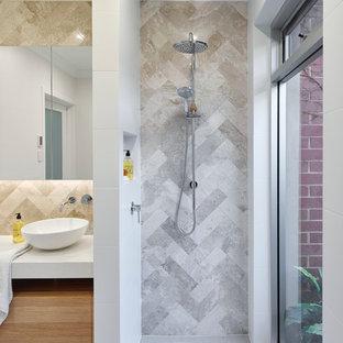 Пример оригинального дизайна: маленькая ванная комната в современном стиле с светлыми деревянными фасадами, открытым душем, раздельным унитазом, серой плиткой, белыми стенами, полом из керамической плитки, душевой кабиной, настольной раковиной, столешницей из искусственного кварца, плиткой из известняка, серым полом, открытым душем и белой столешницей
