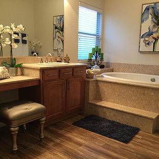 Foto de cuarto de baño principal, clásico renovado, de tamaño medio, con puertas de armario marrones, bañera encastrada, ducha empotrada, baldosas y/o azulejos beige, losas de piedra, paredes beige, suelo de baldosas de cerámica, lavabo encastrado y encimera de terrazo