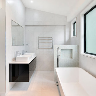 Inspiration for a contemporary bathroom in Brisbane with flat-panel cabinets, black cabinets, a freestanding tub, gray tile, a vessel sink, white floor and white benchtops.