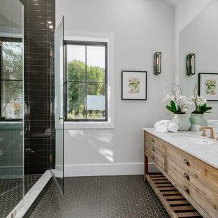Imagen de cuarto de baño campestre, de tamaño medio, con armarios tipo mueble, ducha empotrada, paredes grises, lavabo bajoencimera, encimera de cuarcita, ducha con puerta con bisagras, encimeras blancas, puertas de armario de madera oscura, baldosas y/o azulejos negros y suelo negro