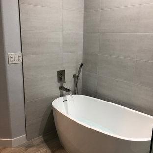 Новый формат декора квартиры: большая ванная комната в современном стиле с угловой ванной, серой плиткой, цементной плиткой, серыми стенами, полом из фанеры, бежевым полом, столешницей из искусственного камня, душем с распашными дверями и белой столешницей
