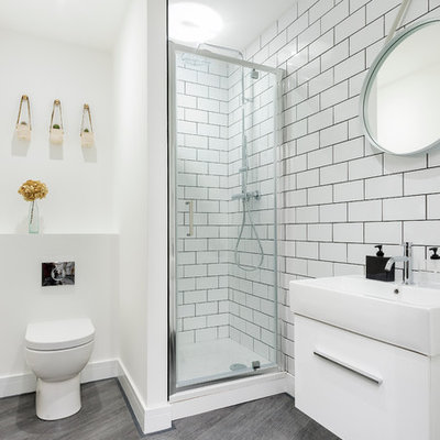 Corner shower - scandinavian white tile and subway tile dark wood floor and gray floor corner shower idea in Dorset with flat-panel cabinets, white cabinets, a one-piece toilet, white walls and a wall-mount sink