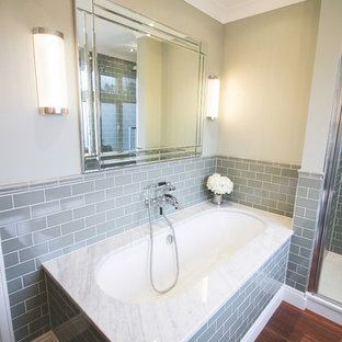 Medium sized retro family bathroom in London with freestanding cabinets, green cabinets, a built-in bath, a walk-in shower, a one-piece toilet, green tiles, metro tiles, green walls, dark hardwood flooring, a pedestal sink, marble worktops, brown floors and a hinged door.