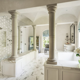 Inspiration for a french country gray tile and marble tile white floor bathroom remodel in Houston with recessed-panel cabinets, gray cabinets, an undermount tub, gray walls and gray countertops