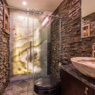 Rustik inredning av ett mellanstort badrum med dusch, med släta luckor, skåp i mörkt trä, en dusch i en alkov, en toalettstol med separat cisternkåpa, brun kakel, grå kakel, porslinskakel, bruna väggar, klinkergolv i keramik, ett fristående handfat och granitbänkskiva