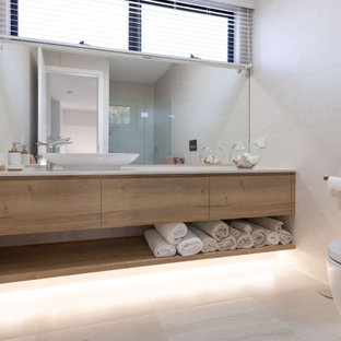 Photo of a mid-sized contemporary bathroom in Gold Coast - Tweed with flat-panel cabinets, medium wood cabinets, gray tile, a vessel sink, grey floor and white benchtops.