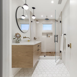 На фото: ванная комната в стиле ретро с плоскими фасадами, фасадами цвета дерева среднего тона, открытым душем, белой плиткой, керамической плиткой, полом из керамической плитки, монолитной раковиной, столешницей из гранита, белым полом, душем с распашными дверями, белой столешницей, тумбой под одну раковину и подвесной тумбой