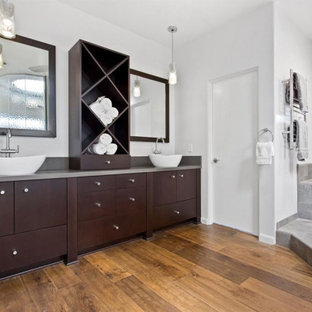 Expansive contemporary master bathroom in Sacramento with flat-panel cabinets, dark wood cabinets, a corner tub, an open shower, a one-piece toilet, gray tile, stone tile, white walls, medium hardwood floors, a vessel sink, zinc benchtops, brown floor, an open shower and grey benchtops.