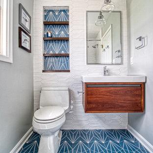 Mittelgroßes Klassisches Duschbad mit flächenbündigen Schrankfronten, hellbraunen Holzschränken, Einbaubadewanne, Duschbadewanne, Toilette mit Aufsatzspülkasten, weißen Fliesen, Keramikfliesen, grauer Wandfarbe, Keramikboden, integriertem Waschbecken, Mineralwerkstoff-Waschtisch, blauem Boden, Duschvorhang-Duschabtrennung und weißer Waschtischplatte in Baltimore