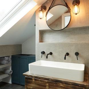 Inspiration för industriella brunt badrum, med släta luckor, skåp i slitet trä, en toalettstol med hel cisternkåpa, grå väggar, ett avlångt handfat och svart golv