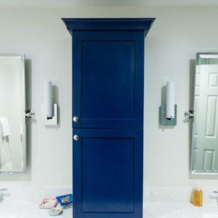 На фото: большие главные ванные комнаты в стиле современная классика с фасадами в стиле шейкер, синими фасадами, ванной в нише, угловым душем, раздельным унитазом, белой плиткой, мраморной плиткой, бежевыми стенами, полом из фанеры, врезной раковиной, мраморной столешницей, коричневым полом, душем с распашными дверями и белой столешницей