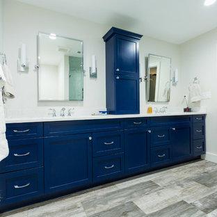Неиссякаемый источник вдохновения для домашнего уюта: большая главная ванная комната в стиле современная классика с фасадами в стиле шейкер, ванной в нише, раздельным унитазом, бежевыми стенами, врезной раковиной, угловым душем, полом из фанеры, коричневым полом, душем с распашными дверями, синими фасадами, белой плиткой, мраморной плиткой, мраморной столешницей и белой столешницей