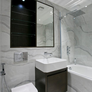 Example of a trendy gray tile bathroom design in London with a vessel sink, flat-panel cabinets, dark wood cabinets and a wall-mount toilet