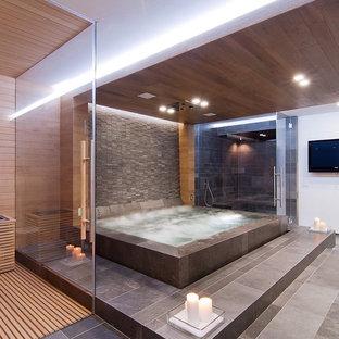 Réalisation d'une douche en alcôve design avec un bain bouillonnant, un carrelage gris et un mur blanc.