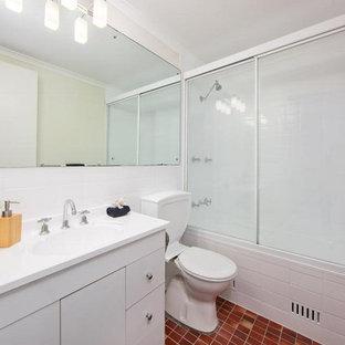 Esempio di una piccola stanza da bagno minimal con ante lisce, ante bianche, vasca ad alcova, vasca/doccia, WC a due pezzi, piastrelle bianche, piastrelle in gres porcellanato, pavimento con piastrelle in ceramica, lavabo integrato, pavimento rosso e porta doccia scorrevole