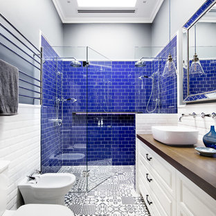 This is an example of a transitional 3/4 bathroom in Melbourne with raised-panel cabinets, white cabinets, a double shower, a two-piece toilet, blue tile, white tile, black walls, ceramic floors, a vessel sink, wood benchtops and a hinged shower door.