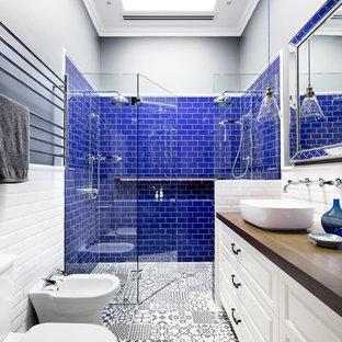 Foto di una stanza da bagno con doccia tradizionale con ante con bugna sagomata, ante bianche, doccia doppia, WC a due pezzi, piastrelle blu, piastrelle bianche, pareti nere, pavimento con piastrelle in ceramica, lavabo a bacinella, top in legno e porta doccia a battente