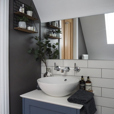 Alcove shower - small scandinavian master white tile and ceramic tile ceramic tile and gray floor alcove shower idea in West Midlands with shaker cabinets, blue cabinets, a wall-mount toilet, gray walls, quartz countertops, a hinged shower door and white countertops