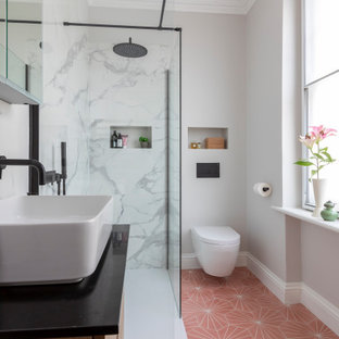 Photo of an eclectic bathroom in London with flat-panel cabinets, medium wood cabinets, a corner shower, white tile, grey walls, a vessel sink, pink floor, an open shower, black benchtops, a single vanity, a floating vanity and a niche.