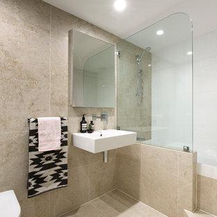 На фото: главные ванные комнаты среднего размера в стиле модернизм с накладной ванной, душем над ванной, инсталляцией, бежевой плиткой, плиткой из травертина, бежевыми стенами, полом из травертина, подвесной раковиной и бежевым полом