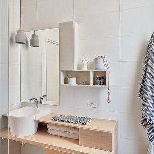 Photo of a mid-sized scandinavian bathroom in Melbourne with furniture-like cabinets, light wood cabinets, a freestanding tub, a corner shower, black tile, grey walls, grey floor, an open shower, grey benchtops, a single vanity and a built-in vanity.
