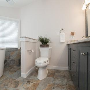 Foto di una stanza da bagno padronale tradizionale di medie dimensioni con ante in stile shaker, ante grigie, vasca ad angolo, vasca/doccia, WC a due pezzi, pareti grigie, pavimento in travertino, lavabo sottopiano e top in granito