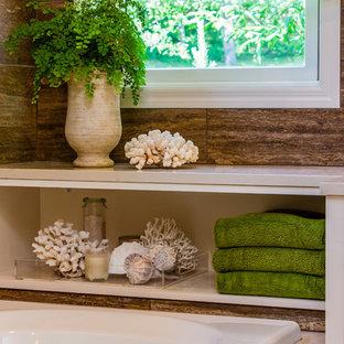 Ispirazione per una grande stanza da bagno padronale minimalista con ante lisce, ante gialle, vasca da incasso, doccia ad angolo, piastrelle marroni, piastrelle in pietra, pareti beige, pavimento in gres porcellanato, lavabo sottopiano e top in quarzo composito