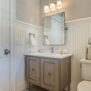 Imagen de cuarto de baño con ducha, romántico, de tamaño medio, con paredes grises, suelo de madera clara, armarios estilo shaker, puertas de armario con efecto envejecido, sanitario de una pieza, encimera de acrílico, lavabo bajoencimera y suelo marrón