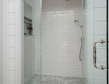 Subway tile shower with rain head, niche and frameless surround