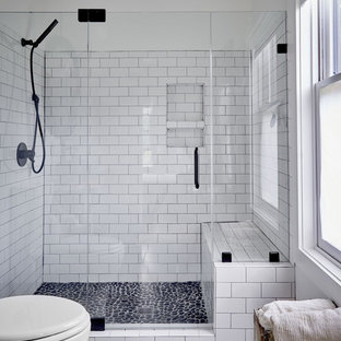 Photo of a mid-sized country bathroom in Other with white tile, porcelain tile, white walls, pebble tile floors, a hinged shower door, an alcove shower and grey floor.