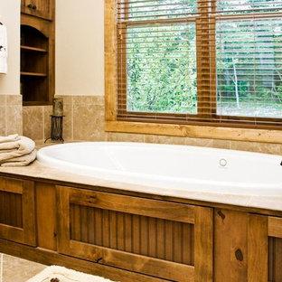 Diseño de cuarto de baño principal, rústico, extra grande, con lavabo bajoencimera, puertas de armario de madera en tonos medios, encimera de granito, bañera empotrada, ducha empotrada, sanitario de dos piezas, baldosas y/o azulejos beige, baldosas y/o azulejos de cerámica, paredes beige, suelo de baldosas de cerámica y armarios con rebordes decorativos