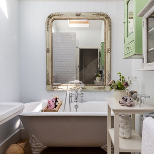 This is an example of a small romantic bathroom in Dorset with glass-front cabinets, green cabinets, a claw-foot bath, white walls and a pedestal sink.