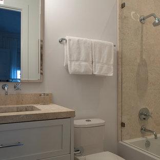 Ispirazione per una stanza da bagno con doccia classica di medie dimensioni con ante in stile shaker, ante bianche, vasca ad alcova, doccia alcova, WC monopezzo, piastrelle beige, piastrelle in travertino, pareti bianche, lavabo sottopiano, top in cemento e porta doccia a battente
