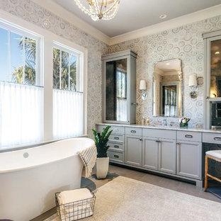 Foto di una stanza da bagno padronale tropicale con ante con riquadro incassato, ante grigie, vasca freestanding e pareti multicolore