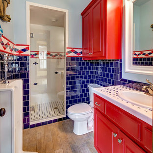 This is an example of a mid-sized traditional kids bathroom in Dallas with raised-panel cabinets, red cabinets, an alcove shower, an urinal, multi-coloured tile, white tile, porcelain tile, multi-coloured walls, medium hardwood floors, a drop-in sink, tile benchtops, brown floor, a hinged shower door and multi-coloured benchtops.