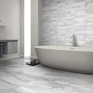 Новые идеи обустройства дома: главная ванная комната среднего размера в стиле модернизм с плоскими фасадами, серыми фасадами, отдельно стоящей ванной, унитазом-моноблоком, серой плиткой, белой плиткой, керамической плиткой, серыми стенами, полом из керамической плитки, настольной раковиной и столешницей из цинка