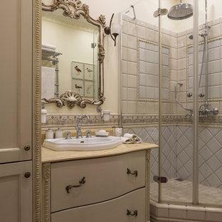 Источник вдохновения для домашнего уюта: маленькая ванная комната в классическом стиле с бежевой плиткой, керамической плиткой, полом из керамической плитки, мраморной столешницей, красным полом, плоскими фасадами, бежевыми фасадами, угловым душем, бежевыми стенами, душевой кабиной, накладной раковиной, душем с распашными дверями и бежевой столешницей