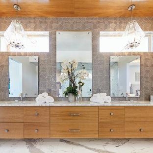 Großes Modernes Badezimmer En Suite mit flächenbündigen Schrankfronten, hellen Holzschränken, freistehender Badewanne, Duschbadewanne, grauen Fliesen, Marmorfliesen, grauer Wandfarbe, Marmorboden, Unterbauwaschbecken, Marmor-Waschbecken/Waschtisch, weißem Boden, Falttür-Duschabtrennung und grauer Waschtischplatte in Dallas