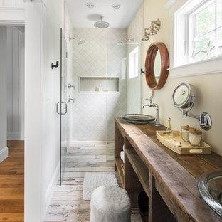 ボストンの中くらいのビーチスタイルのおしゃれなバスルーム (浴槽なし) (オープンシェルフ、濃色木目調キャビネット、ベッセル式洗面器、木製洗面台、バリアフリー、黄色い壁、一体型トイレ、白いタイル、セラミックタイル、セラミックタイルの床、開き戸のシャワー、ブラウンの洗面カウンター) の写真
