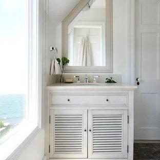 Idées déco pour une salle d'eau bord de mer de taille moyenne avec un lavabo encastré, un placard à porte persienne, des portes de placard blanches, un plan de toilette en marbre, un mur blanc et un sol en galet.