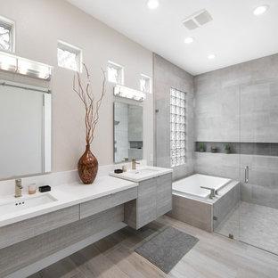 На фото: большая ванная комната в современном стиле с плоскими фасадами, серыми фасадами, накладной ванной, душевой комнатой, серой плиткой, серыми стенами, врезной раковиной, серым полом, душем с распашными дверями и белой столешницей с