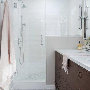 На фото: маленькая главная ванная комната в классическом стиле с фасадами островного типа, темными деревянными фасадами, душем в нише, унитазом-моноблоком, белой плиткой, керамогранитной плиткой, мраморным полом, консольной раковиной, столешницей из искусственного кварца и душем с распашными дверями с