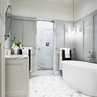 Idee per una stanza da bagno chic con vasca freestanding, pareti grigie e piastrelle di marmo